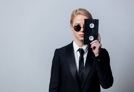 Style businesswoman in a classic black business suit and sunglasses with video tape
