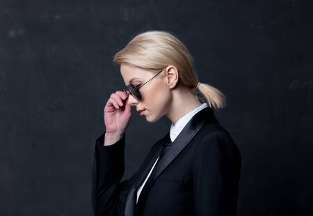 Style businesswoman in a classic black business suit and sunglasses Stock Photo