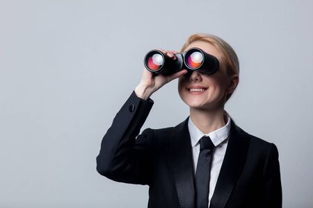 Style businesswoman in a classic black business suit with binoculars Foto de archivo
