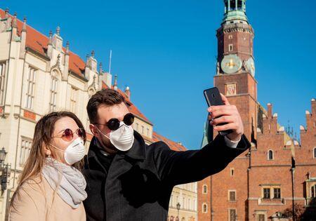 Jeune couple masqué prend un selfie à l'arrière-plan d'un monument à Wroclaw, Pologne
