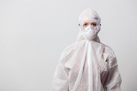 young doctor in protection suit and glasses with mask on white background