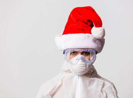 female doctor in protection suit and glasses with mask and in Christmas hat