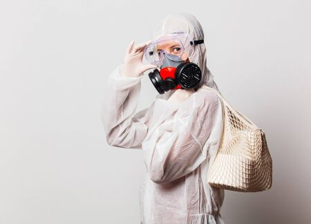 female in protection suit and glasses with mask holds toilet paper Banque d'images