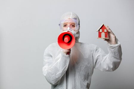 Doctor in protection clothes holds toy house and megaphone, asking to stay at home