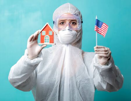 medic in protection clothes holds USA flag and toy house
