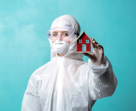 Doctor in protection clothes holds toy house, asking to stay at home Imagens