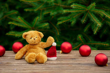 cup of coffee and teddy bear on wooden table with spruce branches on background