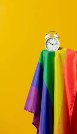 Alarm clock and LGBT flag on yellow background