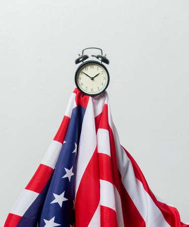 USA flag and alarm clock on white background