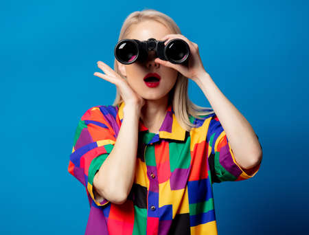 Blonde girl in 90s shirt with binoculars on blue background