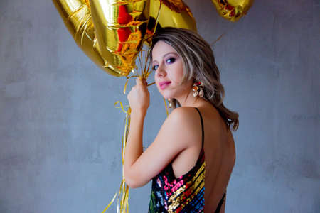 Young woman with golden balloons on her thirty years birthday. Indoor location. Person is in vintage 80th dress and hairstyle. On gray background