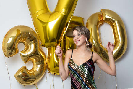 Young woman with golden balloons on her thirty years birthday. Indoor location. Person is in vintage 80th dress and hairstyle. On white background