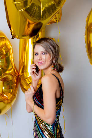 Young woman with golden balloons on her thirty years birthday and calling to friends via mobile phone. Indoor location. Person is in vintage 80th dress and hairstyle. On white background