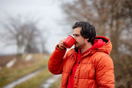 Hipster guy with red mug drink a coffee in countryside