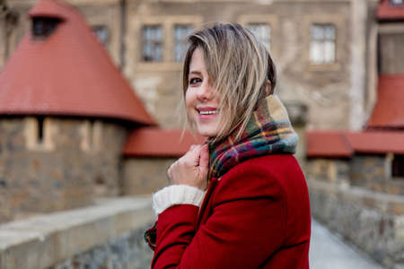 Beautiful woman in red coat stay near castle in winter time. Poland