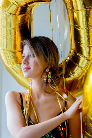 Young woman with golden balloons near window. Indoor location. Person is in vintage 80th dress and hairstyle. At home