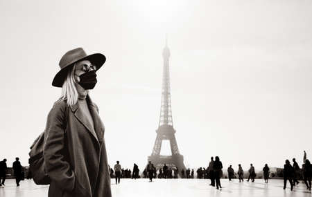 Style woman in face mask and sunglasses with Eiffel tower on background. Image in monchrome style
