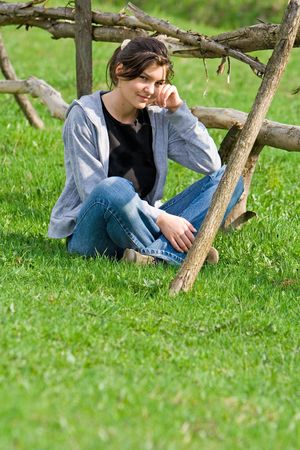 destress: Young woman relaxing on a green field near a wooden fence