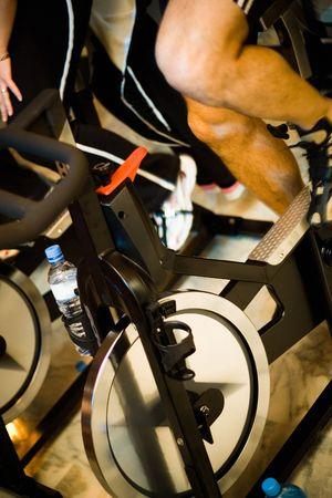 static bike: Active Lifestyle - Man pedalling on stationery bike - Shallow DOF