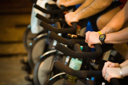 static bike: Active Lifestyle - Men & women pedalling on stationery bikes - Shallow DOF Focus on the hand with the watch