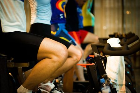 static bike: Active Lifestyle - Men & women pedalling on stationery bikes - Shallow DOF Focus on the 1st personbike