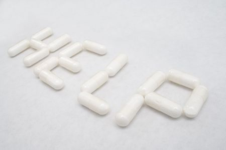 Closeup of HELP text written with capsules on white paper photo