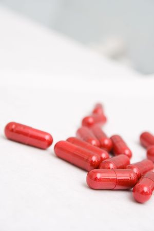Closeup of red capsules on white background - main focus on the first capsule Stock Photo - 416691