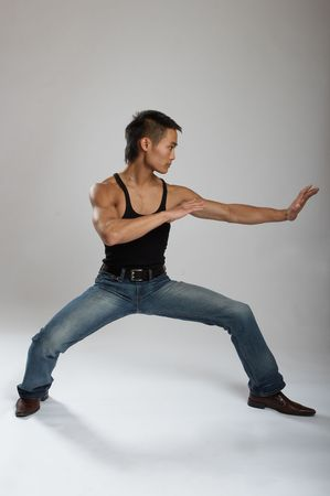 asian abs: Great looking asian guy shot in studio - martial arts pose Stock Photo