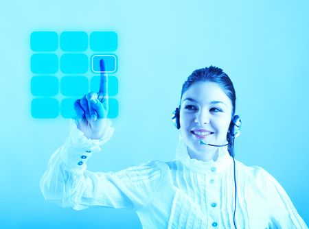 Beautiful Customer Representative with headset smiling during a telephone conversation entering a code on a virtual keyboard