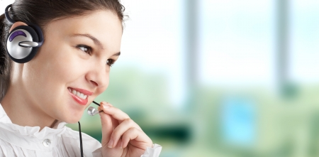 Beautiful Customer Representative with headset smiling during a telephone conversation Stock Photo