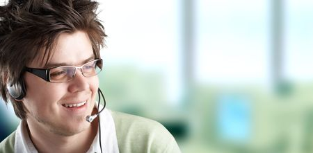 Attractive Customer Representative with headset smiling during a telephone conversation Stock Photo