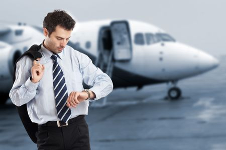 Busy businessman with jacket on his shoulder looking at his watch on the airport - check my portfolio for similar photos Stock Photo - 1149398