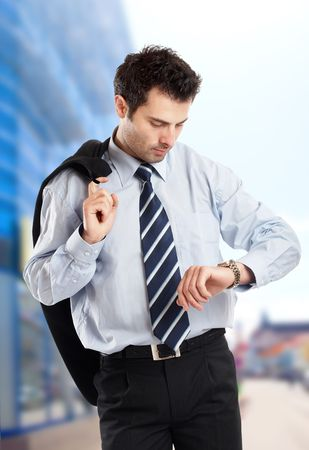 Busy businessman with jacket on his shoulder looking at his watch in front of a glass building - check my portfolio for similar photos Stock Photo - 1149400