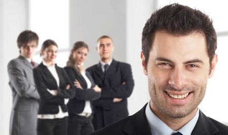 Entrepreneur - with his team behind him in an office environment - people in the background are out of focus - check my gallery for more pictures Stock Photo - 1186302
