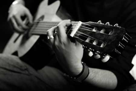 ballad: Rock star plays acoustic guitar on stage with great lights Stock Photo