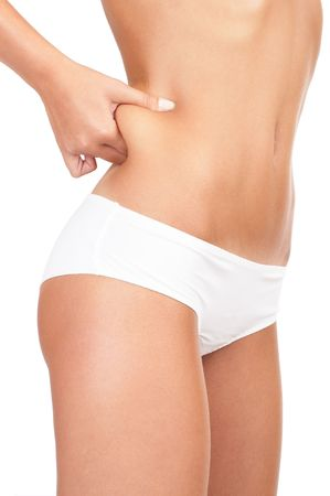 Woman pinching waist for skin fold test - high key shot in studio