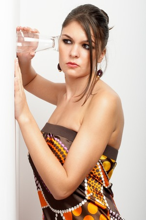 cheated: Beautiful young woman, elegantly dressed eaves-dropping by holding glass to the wall - indignated Stock Photo