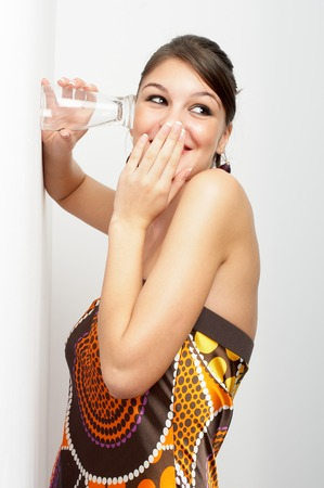 eavesdropping: Beautiful young woman, elegantly dressed eaves-dropping by holding glass to the wall - laughing
