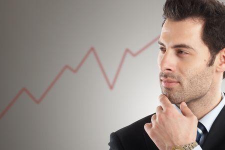 Handsome Businessman looking at line graph in background