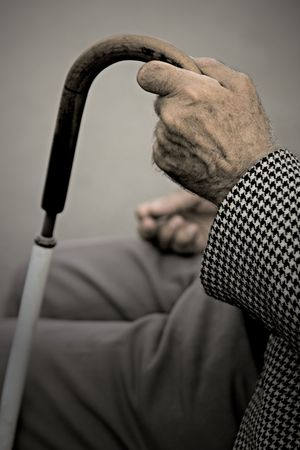 An old man holding his walking stick while standing on the bench