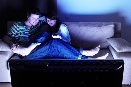 Couple on couch watching TV - having a great time photo
