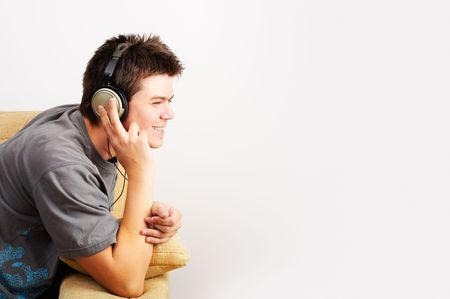 enjoys: Young Man enjoys listening music in headphones Stock Photo