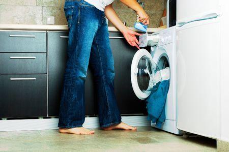hombre sucio: Concepto Hombre poner detergente en la lavadora  Foto de archivo