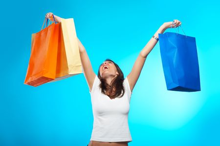 sihlouette: Beautiful Fashion Model with shopping bag over blue background yelling