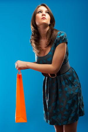 sihlouette: Beautiful Fashion Model with shopping bag over blue background Stock Photo