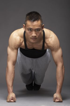 Young asian man doing pushup over gray background Stock Photo - 3111955