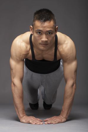 asian sport: Young asian man doing pushup over gray background
