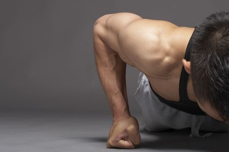 Young asian man doing pushup over gray background Stock Photo - 3111933
