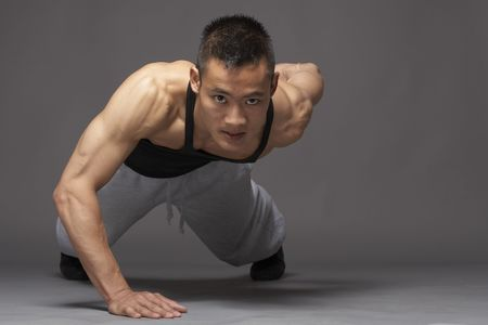 pushup: Young asian man doing pushup over gray background
