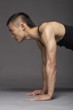 Young asian man doing pushup over gray background photo